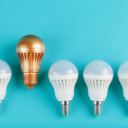 one-gold-led-light-bulb-is-higher-stands-out-from-row-white-lamps-blue-wall_94046-4701