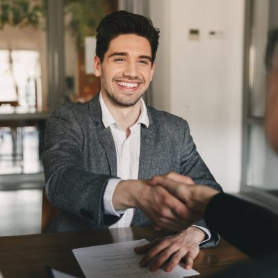Business, career and placement concept - happy caucasian man 30s rejoicing and shaking hands with employee when was recruited during interview in office