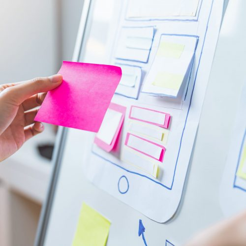 Mobile Application Designers are development on smartphone and pink paper note on hand, creative sketch planning.