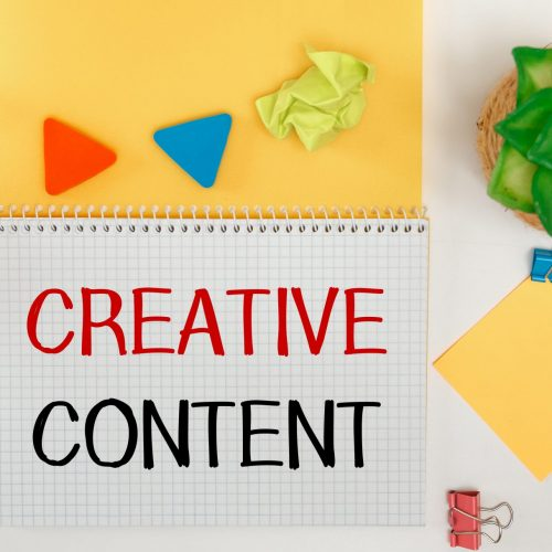 Text CREATIVE CONTENT. Inspirational quotes on notebook and office supplies