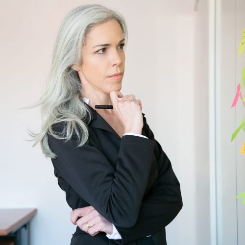 Thoughtful gray-haired businesswoman reading notes on glass